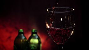 Pouring red wine into glass shooting, two bottles and dark red background, high quality video.  stock video