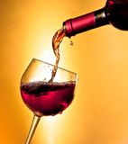 Pouring red wine in the glass tilted Royalty Free Stock Photos