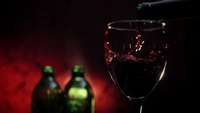 Pouring red wine in glass, two bottles and dark red background, romantic atmosphere during date.  stock video