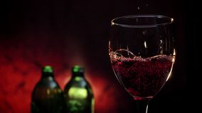 Pouring red wine in glass, two bottles and dark red background, romantic atmosphere, high quality video.  stock video