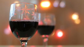 Pouring red wine into glass. Two glasses, lights stock video footage
