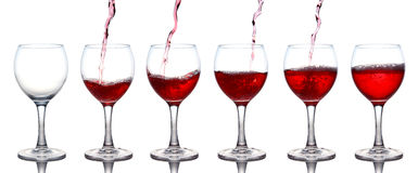 Pouring of red wine in a glasss isolated on white Stock Photo