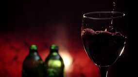 Pouring red wine in goblet, liquid splashing everywhere, two bottles and crimson background, 4k video.  stock video