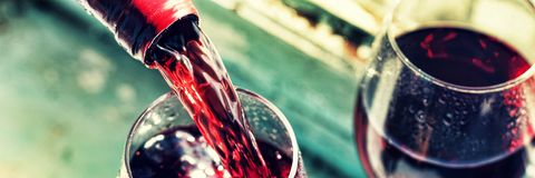 Pouring red wine. Wine in a glass, selective focus, motion blur, Stock Image