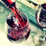 Pouring red wine. Wine in a glass, selective focus, motion blur,. Red wine in a glass. Sommelier pouring the wine into the glass. Thanksgiving Day, Valentine`s Stock Photos