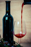 Pouring red wine into wine glass on wood background Royalty Free Stock Photography