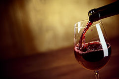 Pouring red wine into a wineglass Royalty Free Stock Photos
