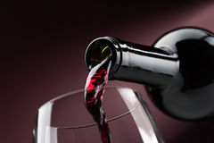 Pouring red wine into a wineglass. Pouring red wine from a bottle into a wineglass: wine tasting and celebration Royalty Free Stock Photos