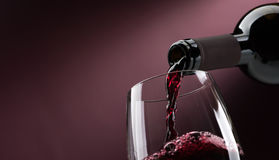 Pouring red wine into a wineglass. Pouring red wine from a bottle into a wineglass: wine tasting and celebration Royalty Free Stock Photo