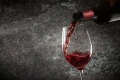 Pouring red wine into wineglass. Copy space stock images
