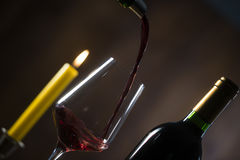 Pouring red wine into wineglass from green bottle. Brown background stock image
