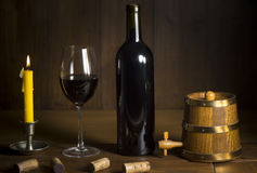 Pouring red wine into wineglass from green bottle. Brown background stock photos