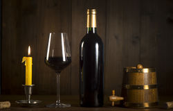 Pouring red wine into wineglass from green bottle. Brown background royalty free stock images