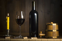 Pouring red wine into wineglass from green bottle. Brown background royalty free stock photography