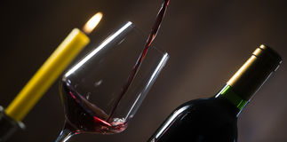 Pouring red wine into wineglass from green bottle. Brown background stock photo