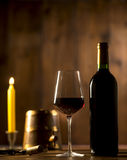 Pouring red wine into wineglass from green bottle. Brown background stock photography