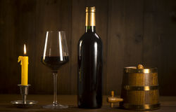 Pouring red wine into wineglass from green bottle. Brown background royalty free stock photos