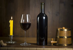 Pouring red wine into wineglass from green bottle. Brown background royalty free stock image