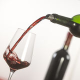 Pouring red wine into wineglass from green bottle. White background royalty free stock photo