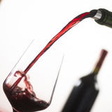 Pouring red wine into wineglass from green bottle. White background royalty free stock photography