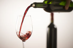Pouring red wine into wineglass from green bottle. White background stock image