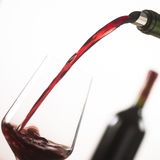 Pouring red wine into wineglass from green bottle. White background royalty free stock images