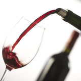 Pouring red wine into wineglass from green bottle. White background stock photography