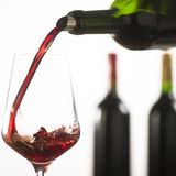 Pouring red wine into wineglass from green bottle. White background stock photo