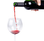 Pouring red wine into a wineglass. Hand pouring red wine into a wineglass from an unlabelled wine bottle isolated on white stock photography