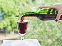 Pouring red winen on a green background. The girl pours red wine in a glass on a green background Royalty Free Stock Images