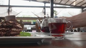 Pouring rich tea in glass cup from in transparent teapot on cafe table. Tea glass and chocolate pie on wooden table in. Summer cafe. Tea drinking in stock video footage