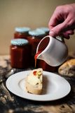 Pouring rose hip jam on bread Royalty Free Stock Photos