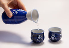 Pouring sake. Into a cup with an asian design Stock Image