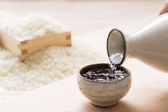 Free Pouring Sake Into A Small Japanese Cup Stock Photography - 167111632