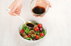Pouring salad with sauce Royalty Free Stock Photography