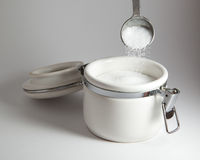 Pouring salt. Into a white container Royalty Free Stock Images