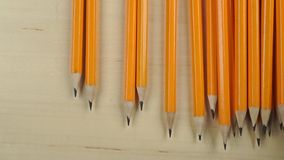 Pouring same pencils on light wooden table, view from above stock footage