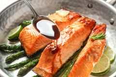 Pouring sauce onto tasty cooked salmon in frying pa. N, closeup Stock Photos