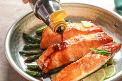Pouring sauce onto tasty cooked salmon in frying pan. Closeup Royalty Free Stock Photography