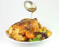 Pouring Sauce over Whole Roasted Chicken. Accompanied with vegetable salad and potatoes Stock Photos