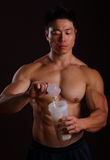 Pouring a scoop of protein shake. Asian Man Pouring a scoop of Protein Shake in to the Jar Royalty Free Stock Photos