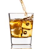 Pouring scotch whiskey in glass with ice cubes on white Royalty Free Stock Photos