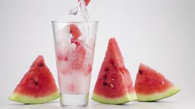 Pouring Soda Water with the Ice and Watermelon Cubes into a Glass stock video footage