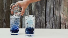 Pouring soda water over a concentrated syrup made out of blue pea flower tea Clitoria Ternatea stock video