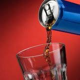 Pouring a soft drink in a glass. Pouring a refreshing sugary soft drink from a can into a glass stock photos