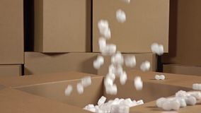 Pouring soft polystyrene pieces into big carton. Shockproof packaging material. Safety, security and insurance concepts