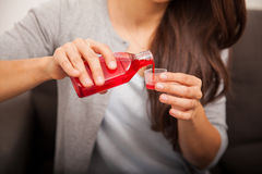 Pouring some cough syrup Royalty Free Stock Images