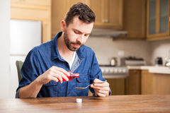 Pouring some cough syrup at home. Young man serving a spoonful of cough syrup to ease his throat Royalty Free Stock Photo