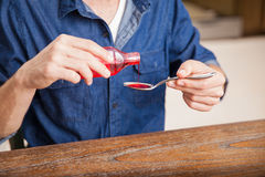 Pouring some cough syrup in a spoon. Closeup of a young man serving a spoonful of cough syrup at home Royalty Free Stock Photos