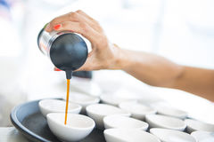 Pouring soy sauce into small cup stock image